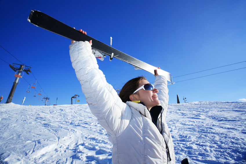 Happy winner girl holding ski against the blue sky.